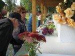 Exposition de fleurs et légumes plantés localement. Le public admire après que le juri ait décerné les prix par catégorie.