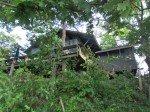 La maison depuis le lac, enfouie dans la végétation.